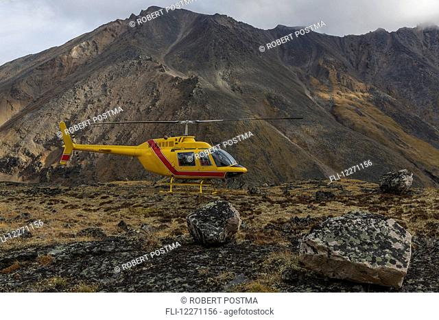 Yellow helicopter sitting on a mountain top in Tombstone Territorial Park; Yukon, Canada