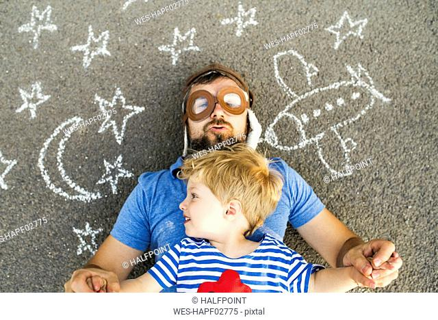 Portrait of mature man wearing pilot hat and his little son lying on asphalt painted with airplane, moon and stars