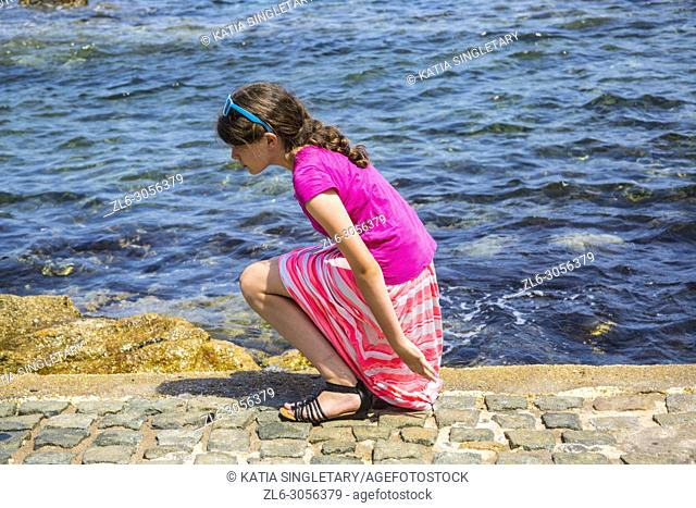 A preteen all dress in pink playing on the side of the bay of Saint Tropez. We can see the city village of Saint Tropez in France behind her