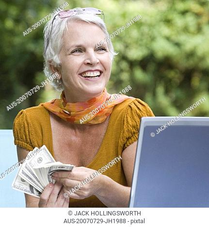 Mature woman holding paper currency and smiling