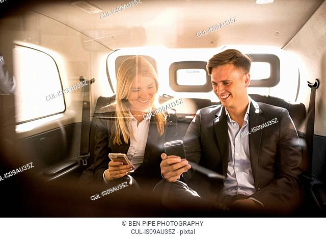 Businessman and businesswoman using smartphone in black cab, London, UK