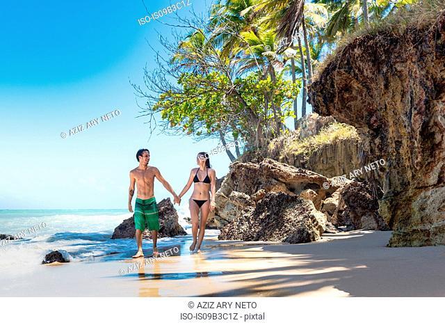 Young couple strolling on beach, Taiba, Ceara, Brazil