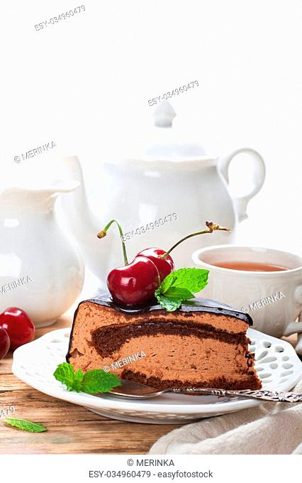 Piece of delicious chocolate mousse cake with cherries and mint over white with copy space. High tea concept. Selective focus. Space for text