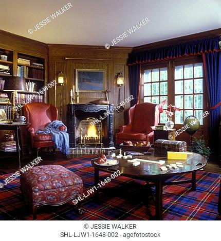 FAMILY ROOM - Paneled walls, fireplace, dark blue valance and curtains with red trim, red leather wing chairs, red and blue plaid carpet,built in book shelves