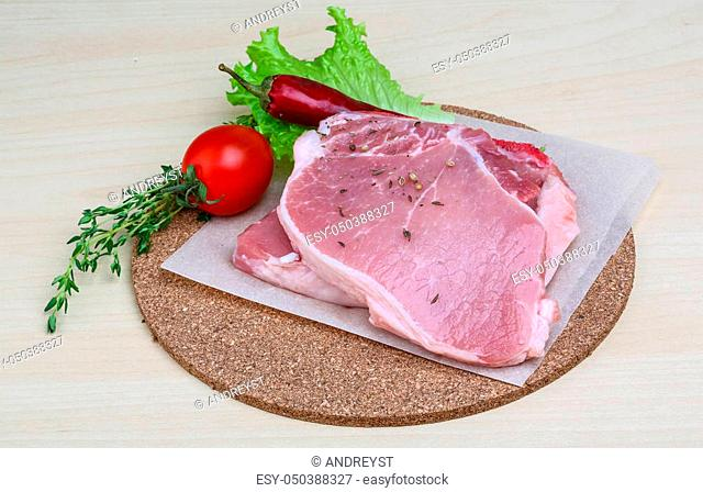 Raw pork steak with thyme and red pepper