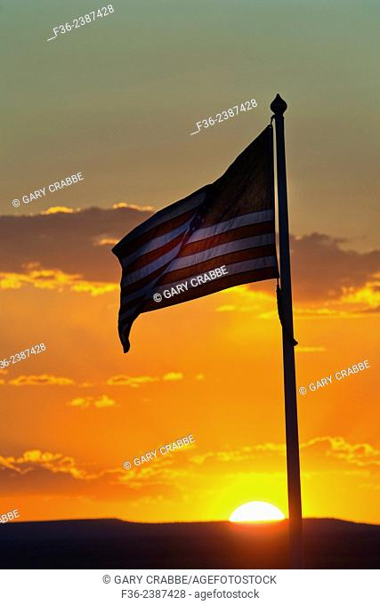Sunset behind American Flag waving in the breeze near Winslow, Arizona
