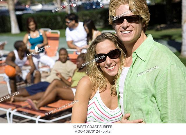Portrait of Young Couple in Sunglasses Others in Background