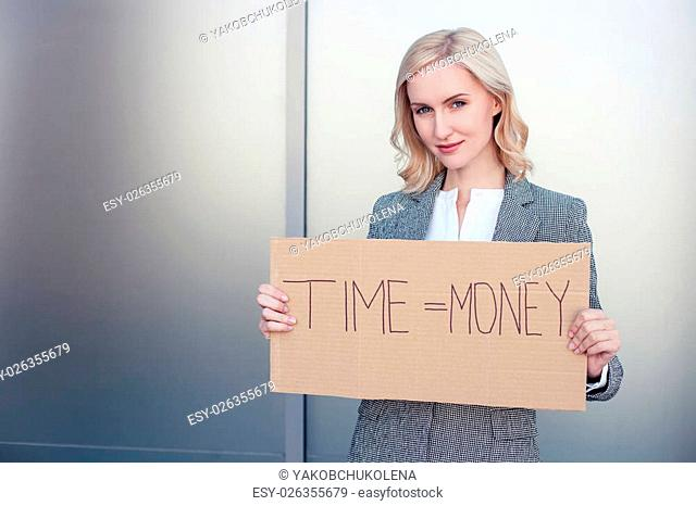 Time is money. Successful woman in formalwear is standing and holding a billboard. She is looking forward confidently and smiling