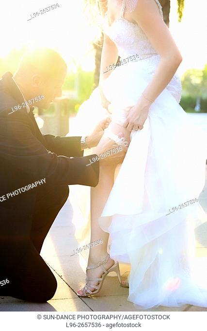 groom putting on brides garter