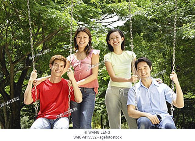 Men on swings, women standing next to them