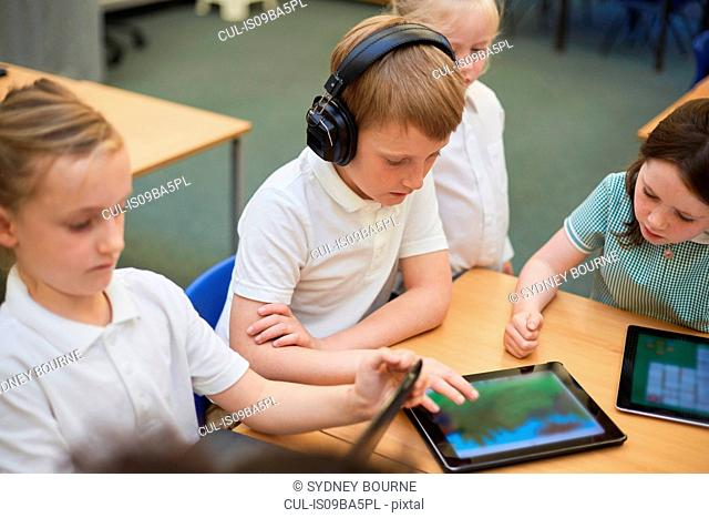 Schoolboys and girls looking at digital tablets in class at primary school