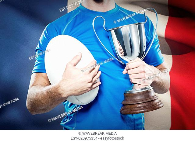 Composite image of rugby player holding trophy and ball