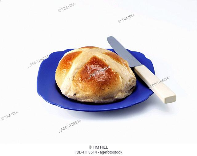 Easter hot cross bun on a blue plate on a white background