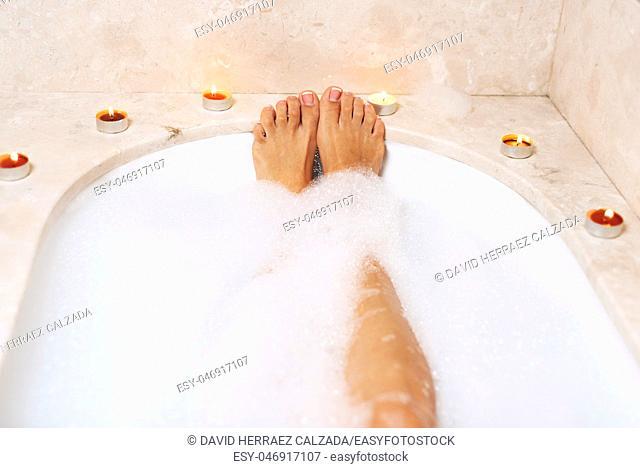 Woman legs in bath foam. Relaxation in spa