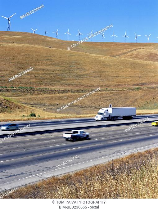 Cars and trucks driving on freeway near wind farm
