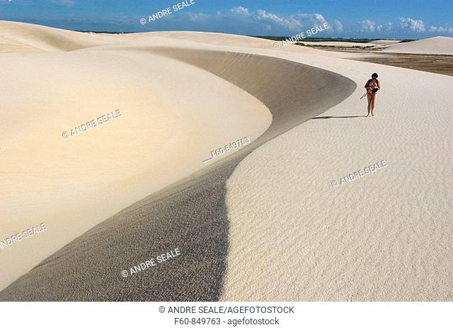 Tourist walks on the sand dunes of Lencois Maranhenses National Park, Santo Amaro, Maranhão, Brazil