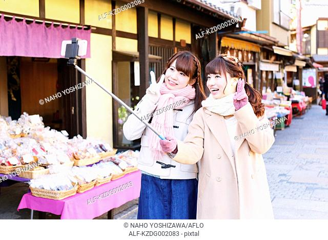Two young Japanese women taking a selfie in Kawagoe old town, Japan