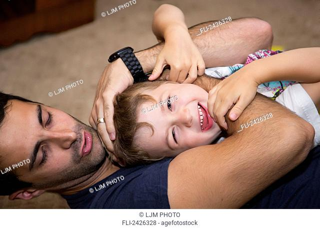 Father play fighting and wrestling with his young son; Edmonton, Alberta, Canada