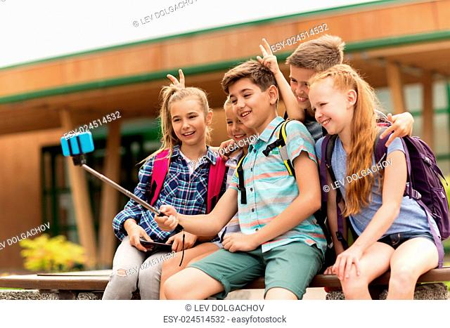 primary education, technology, friendship, childhood and people concept - group of elementary school students with backpacks sitting on bench and taking picture...
