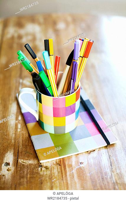Marker and felt tip pens in desk organizer on wooden table