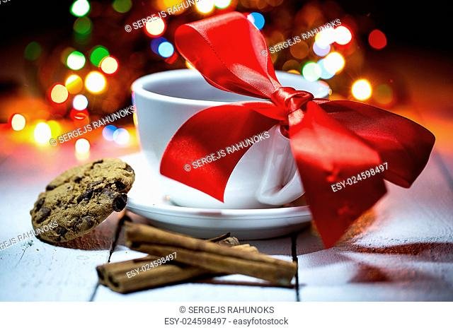 Cup of coffe with a bow on it. Few sticks of cinnamon and a cookie. The background is covered with colorful lights