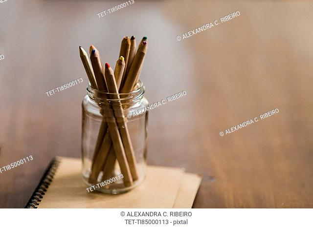 Coloured pencils in jar on book