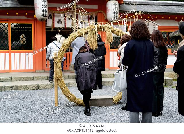 Woman stepping through a large straw ring at a Japanese Shinto shrine for Chinowa Kuguri rite, summer purification ritual, at Uji-jinja, Uji Shrine in Uji