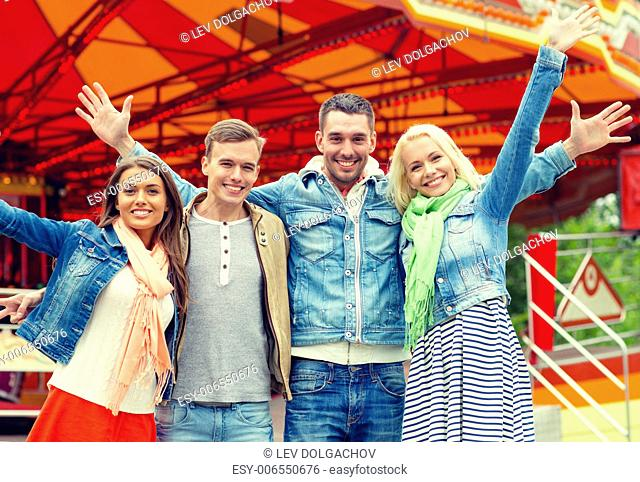 leisure, amusement park and friendship concept - group of smiling friends waving hands with carousel on the back
