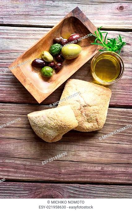 Pickled olives with bread and olive oil on a rustic table