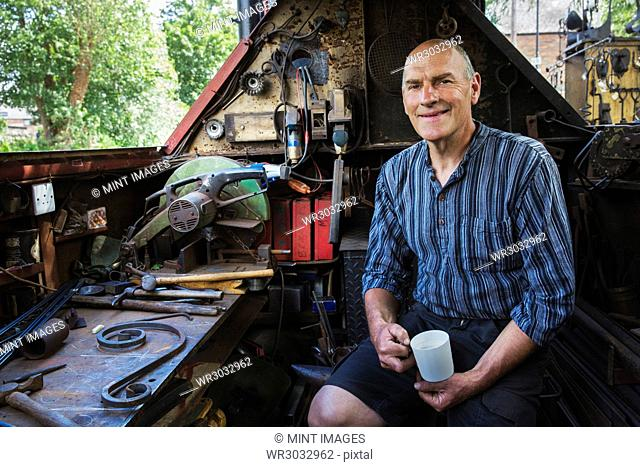 Blacksmith sitting on a working boat, a narrowboat on a waterway, holding a mug, smiling at camera