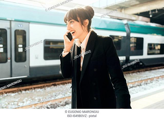 Businesswoman using mobile phone in train station, Milan, Italy