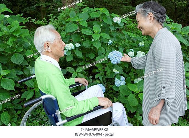 Japan, Tokyo Prefecture, Senior man watching senior woman holding flower, smiling