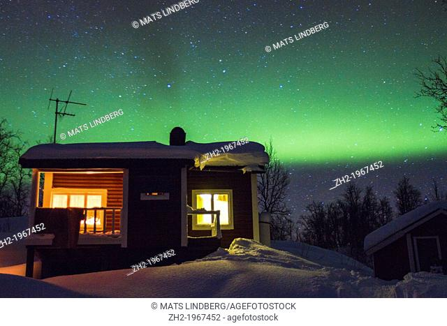 Cottage with northern light, aurora borealis in background in winter time at Riksgränsen in swedish lapland