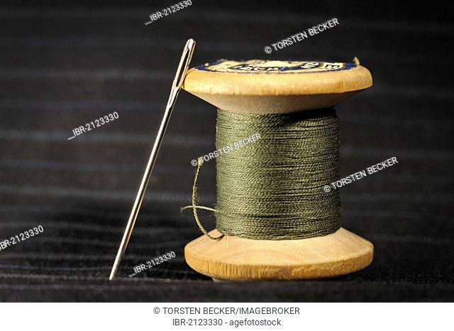 Wooden spool with green thread and darning needle, on black striped cotton