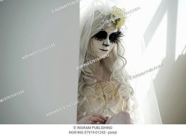 Halloween witch. Beautiful woman wearing santa muerte mask and wedding dress