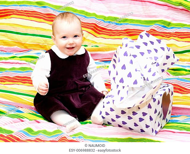 Happy eight month baby girl with wrapped gift