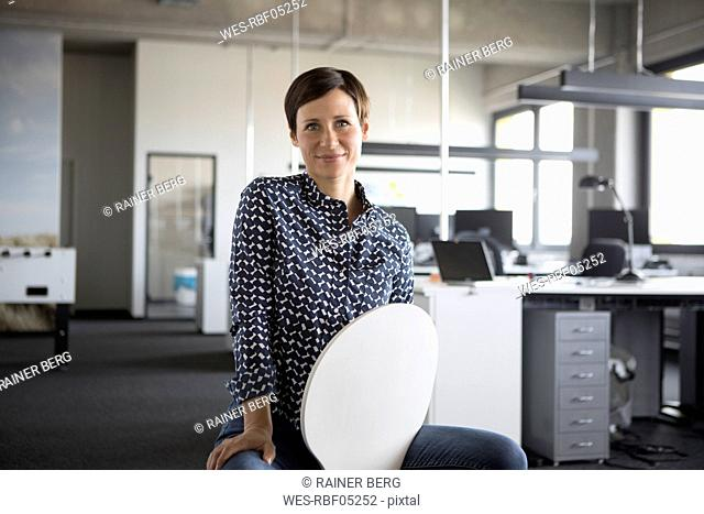 Portrait of smiling businesswoman in office sitting on chair