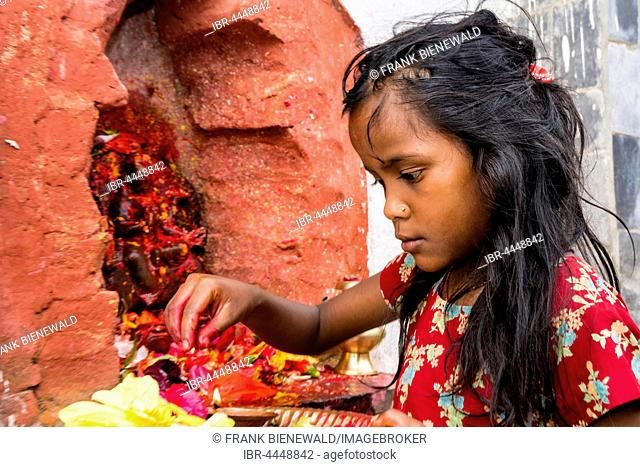 Little girl offering Prasad to statues of gods outside Khadga Devi Temple, Hindu festival Darsain, Bandipur, Tanahun District, Nepal