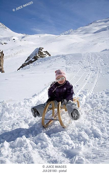 Young girl sledding in snow on winter day
