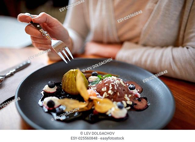 food, new nordic cuisine and people concept - woman eating chocolate ice cream dessert with blueberry kissel, honey baked fig and greek yoghurt at restaurant