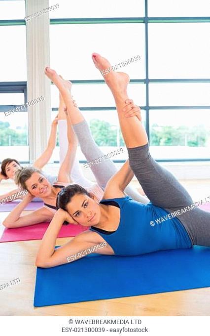 Women on mats stretching legs in fitness studio