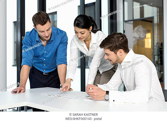 Meeting of three business people in a conference room