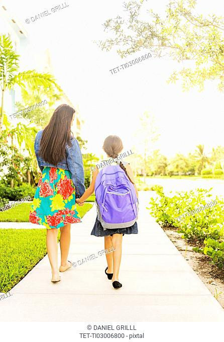 Rear view of girl (6-7) holding hands with her mom outdoors