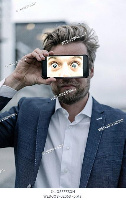 Businessman holding cell phone in front of his eyes