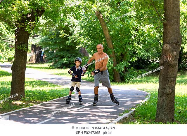 Grandfather teaching grandson roller skating outdoors