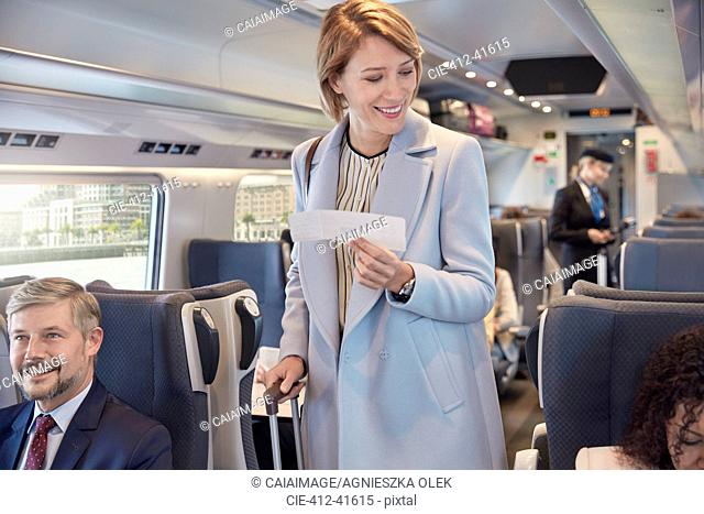 Businesswoman with ticket boarding passenger train, finding seat
