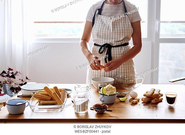 Woman separating egg for preparing Tiramisu