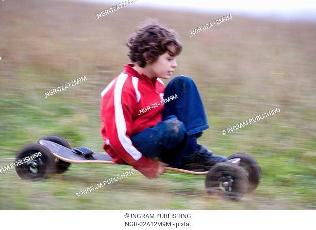 Boy riding a mountain board in a field