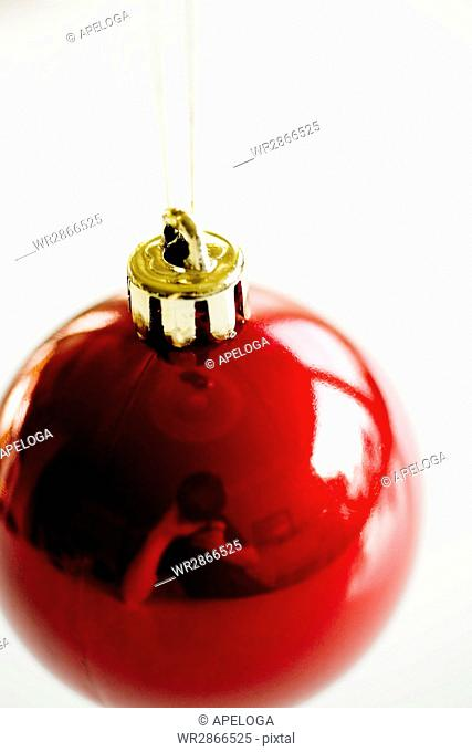Close-up of red bauble on white background