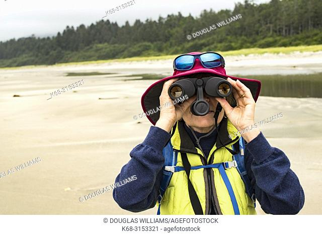 Woman with binoculars on Flores Island, off the west coast of Vancouver Island, British Columbia, Canada
